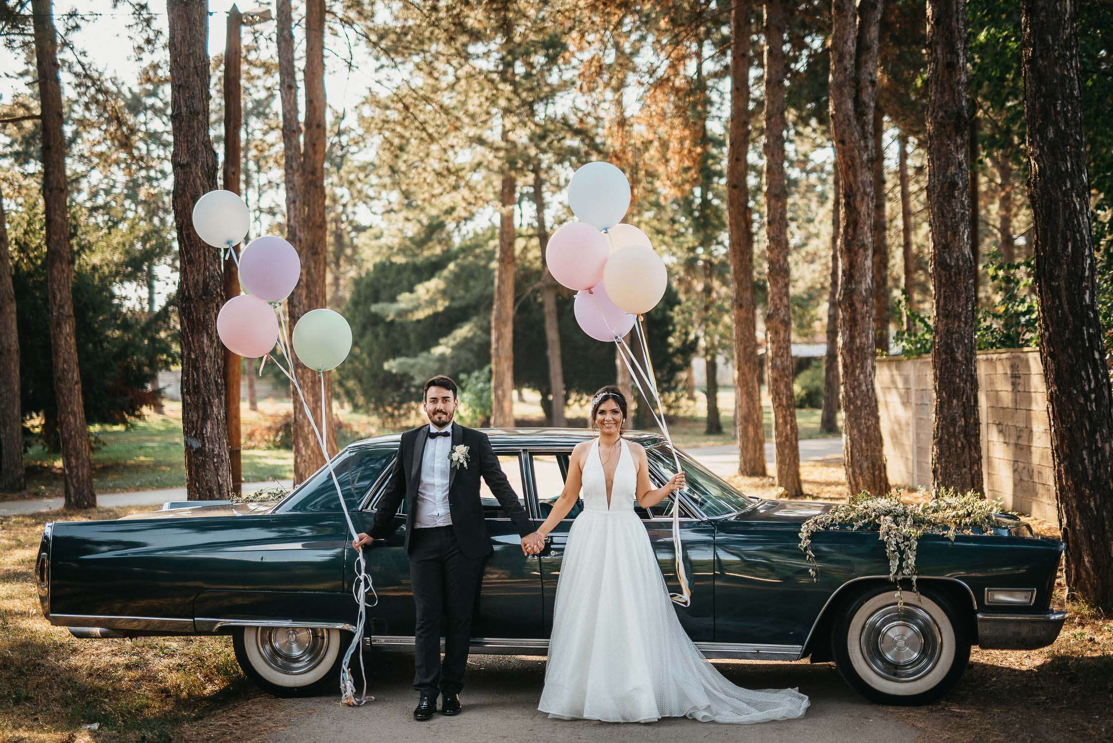 bride and groom posing with balloons
